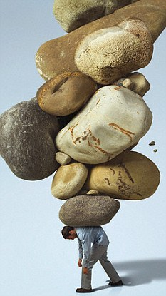 man weighed down by rocks